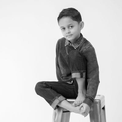 Contemporary portrait black and white of young boy in studio.