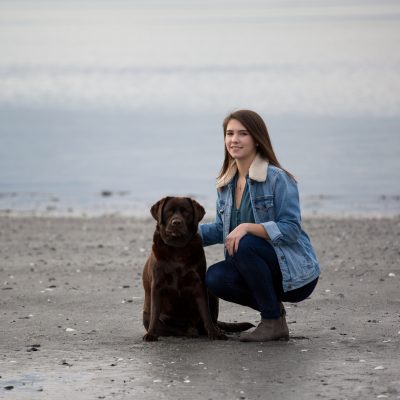 High School Senior portrait. Using natural light in a fashion inspired style. Women on beach with her dog.