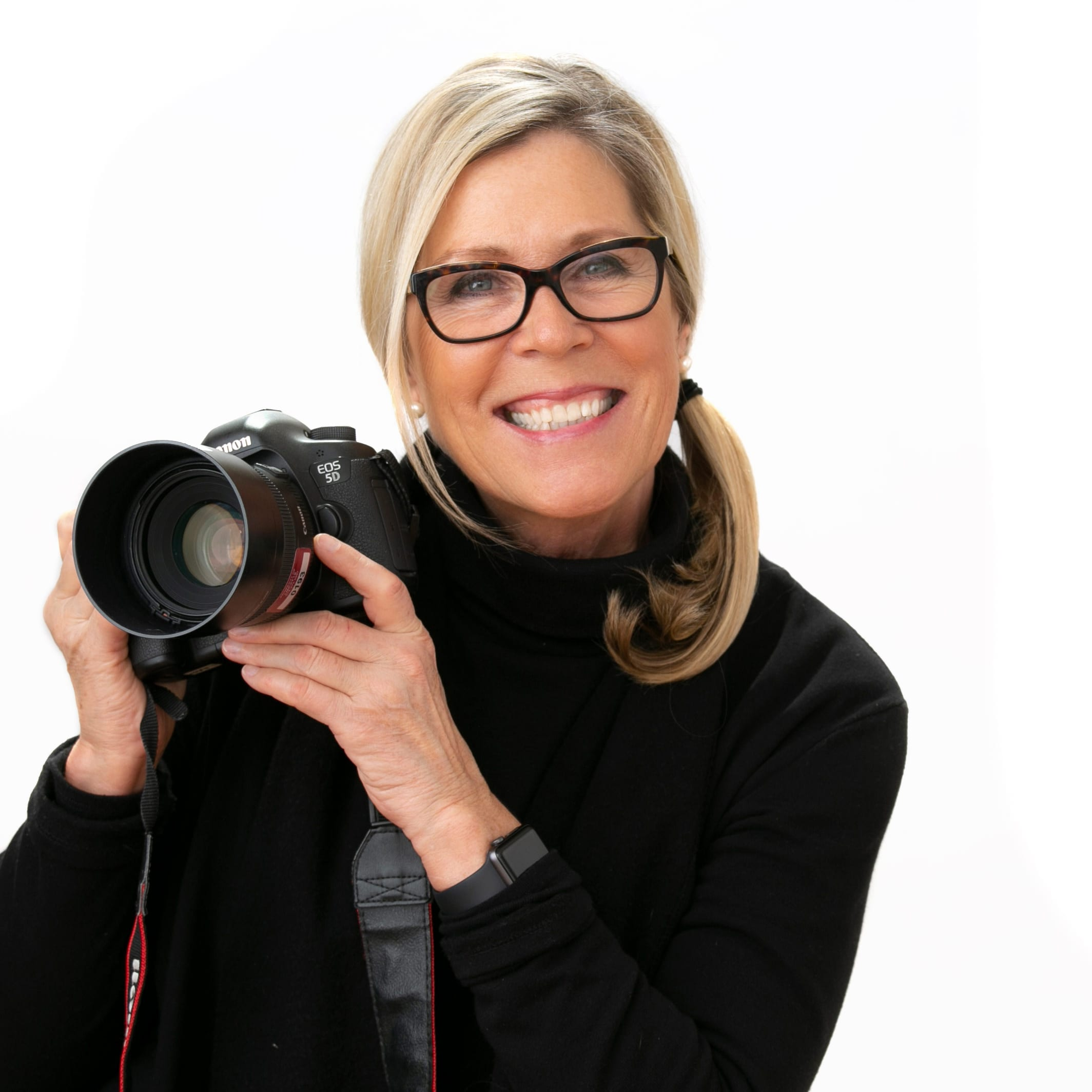 Louise Michaud Photographer holding camera and smiling
